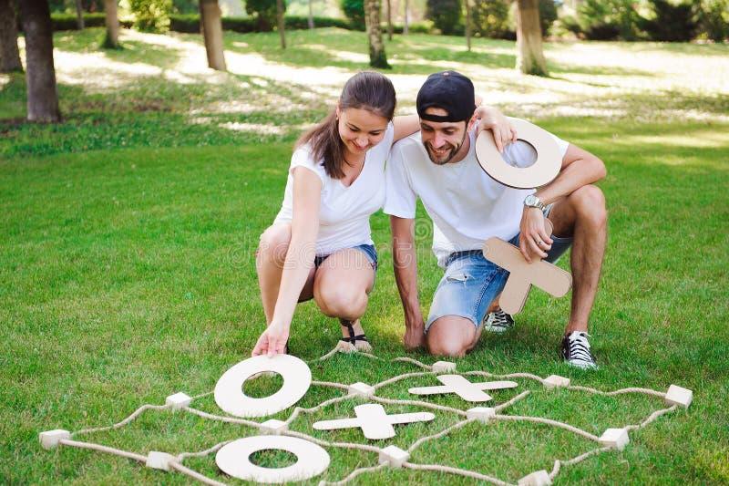 Lachende jongen en meisjes speel tic-TAC-teen in het park stock foto