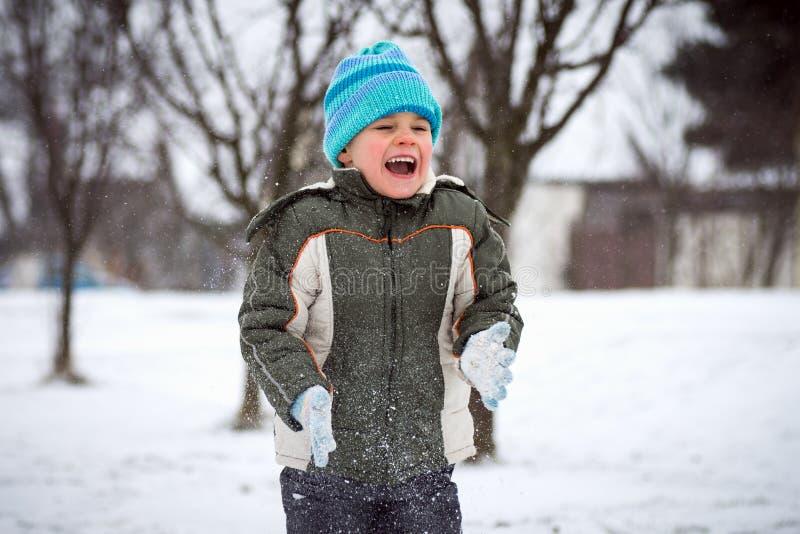Lachende jongen in sneeuwval stock afbeeldingen