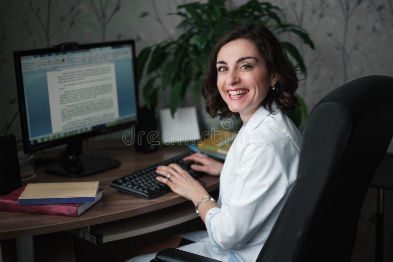 Lachende junge Ärztin in einer weißen medizinischen Robe, die an einem Tisch sitzt Auf dem Tisch Bücher, ein Computermonitor und  lizenzfreies stockfoto