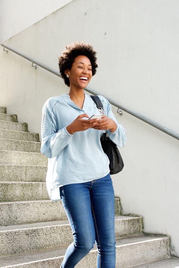 Lachende junge afrikanische Frau, die hinunter die Schritte geht stockfotografie