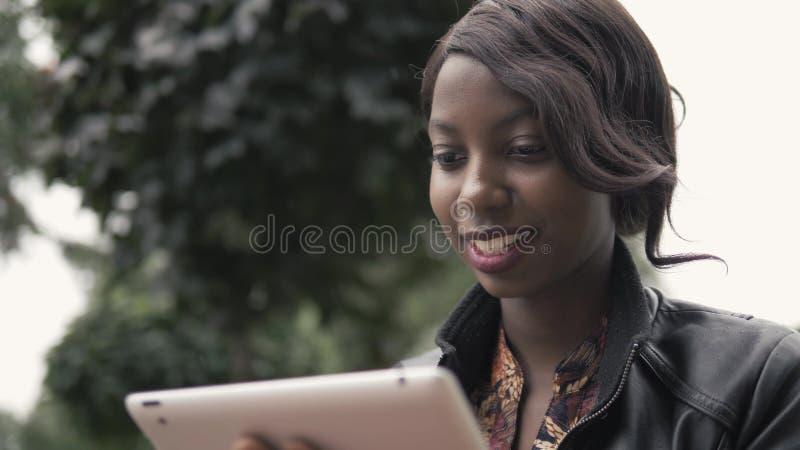 Lachende junge Afroamerikaner-Frau, die einen Noten-Auflagen-Tablet-PC, schwarzer Student im Freien nach dem Hochschulhandeln häl stockfoto