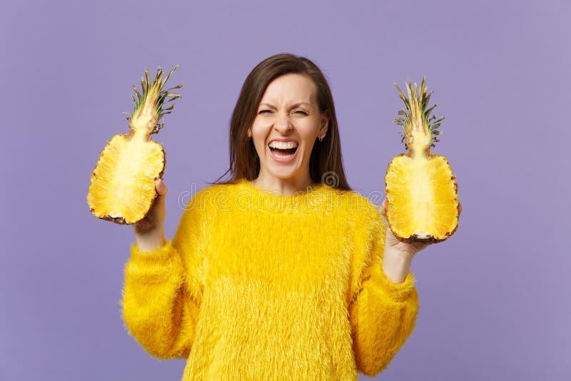 Lachende junge Frau in der Pelzstrickjacke, die in den Hand-halfs der frischen reifen Ananasfrucht lokalisiert auf violetter Past stockfoto