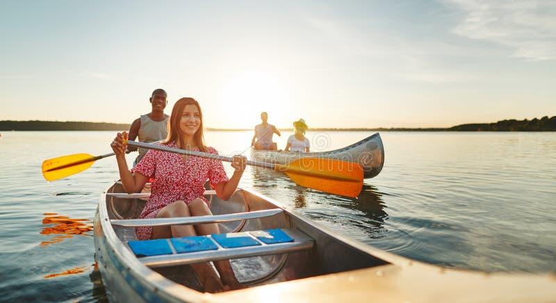 Lachende junge Frau, die Spaß mit Freunden in einem See hat lizenzfreie stockbilder