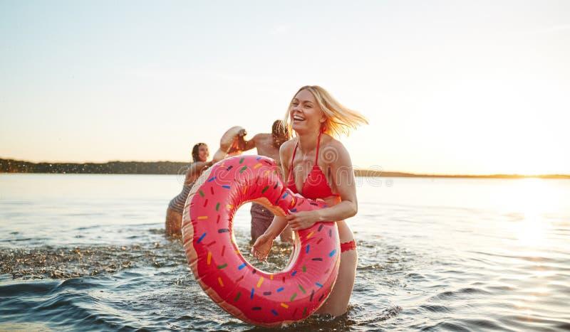 Lachende junge Frau, die Spaß mit Freunden in einem See hat lizenzfreies stockfoto