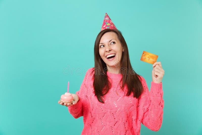 Lachende junge Frau im gestrickten rosa Strickjackengeburtstagshut, der oben in der Hand Kuchen des Griffs mit der Kerzenkreditka stockfotografie