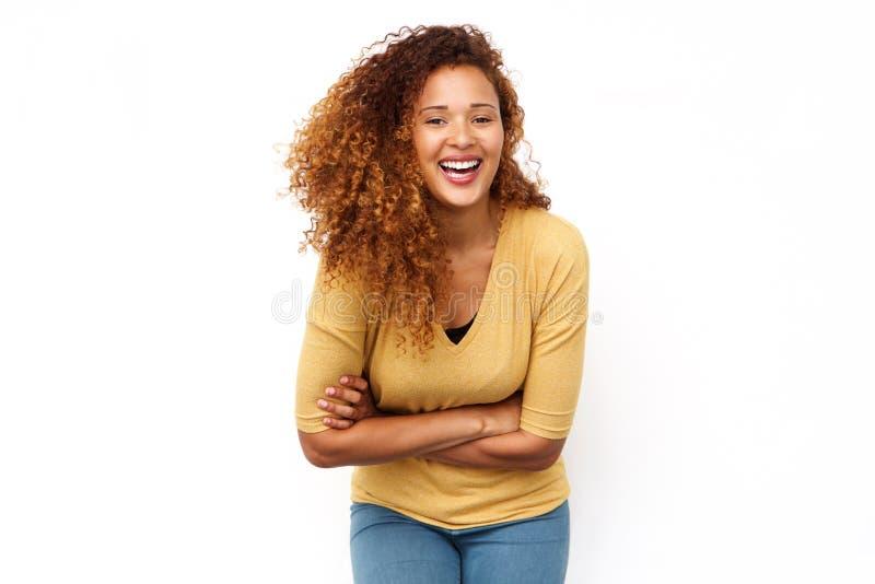 Lachende junge Frau mit dem gelockten Haar gegen lokalisierten weißen Hintergrund stockfoto