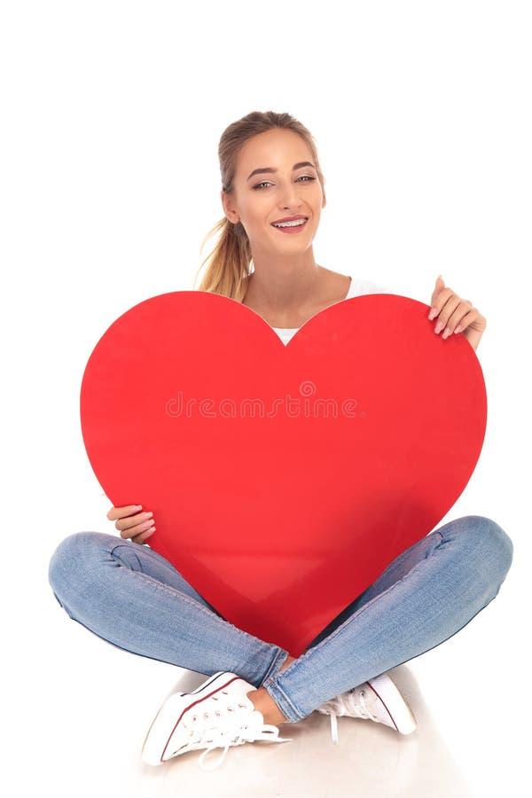 Lachende junge Frau mit den Klammern, die ein großes rotes Herz halten lizenzfreies stockbild