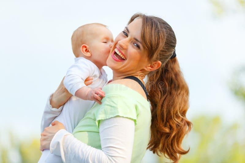Lachende junge Mutter, die ihr Schätzchen umarmt lizenzfreie stockfotografie
