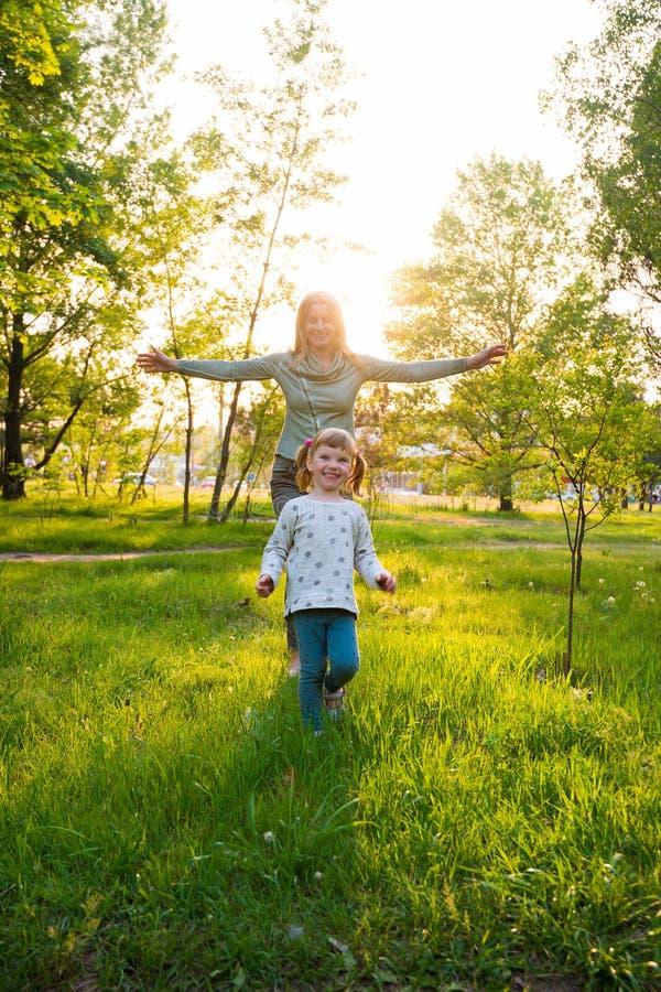 Lachende junge Mutter und ihre kleine Tochter, mit den offenen Armen lizenzfreie stockfotos