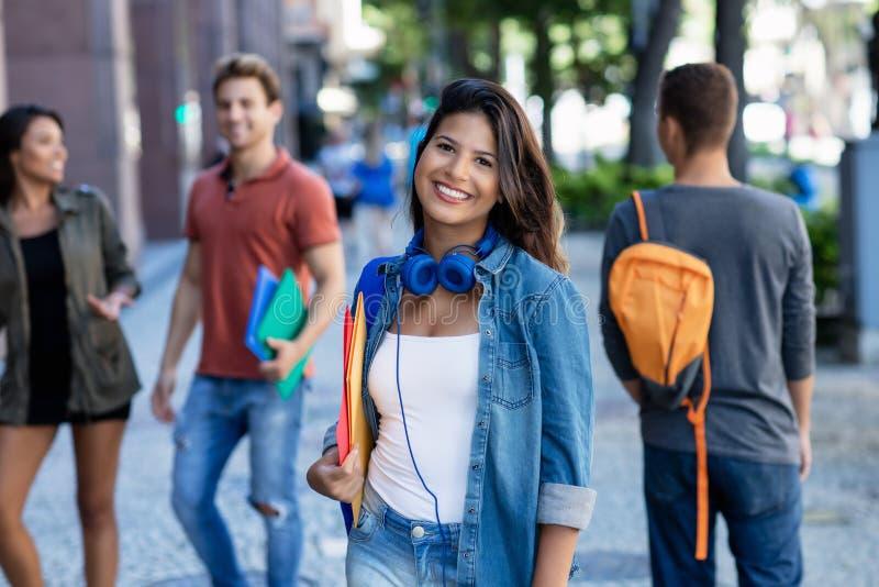 Lachende Kaukasische jonge volwassen vrouw die in stad met groep studenten lopen royalty-vrije stock foto's