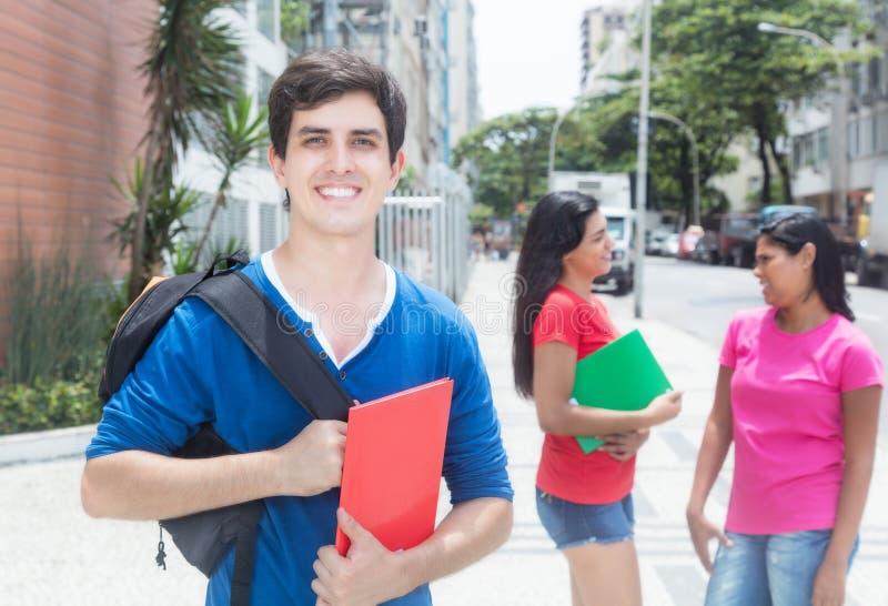 Lachende Kaukasische mannelijke student met vrienden stock afbeeldingen