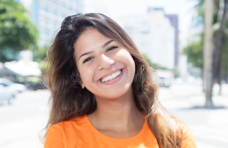 Lachende Kaukasische vrouw in een oranje overhemd in de stad royalty-vrije stock afbeeldingen