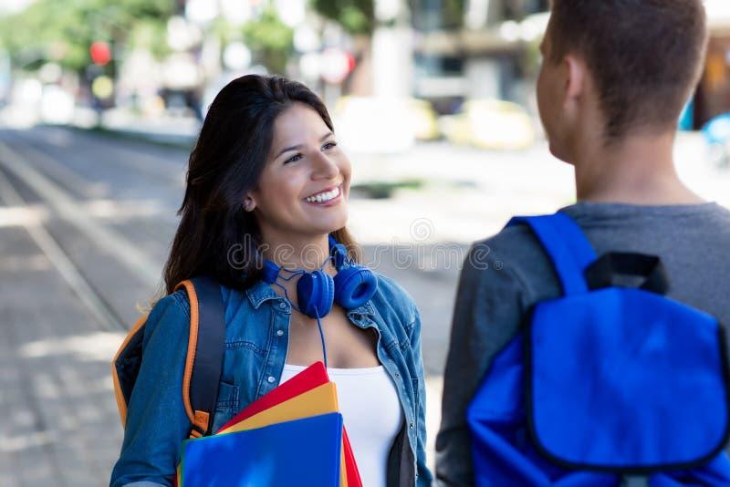 Lachende Kaukasische vrouwelijke student die met mannelijke student in stad spreken stock afbeelding