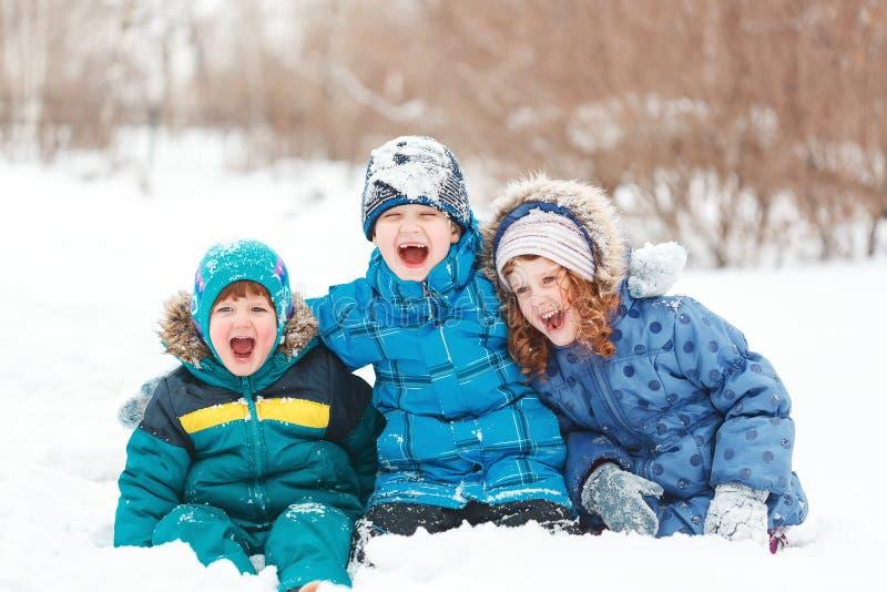 Lachende Kinder, die auf einem Schnee sitzen stockfotografie