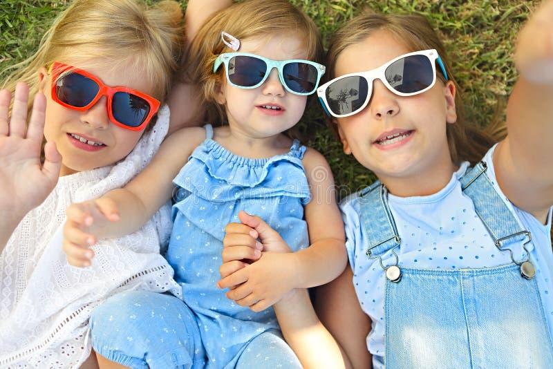 Lachende kinderen die tijdens de zomerdag ontspannen op het groene gras stock foto