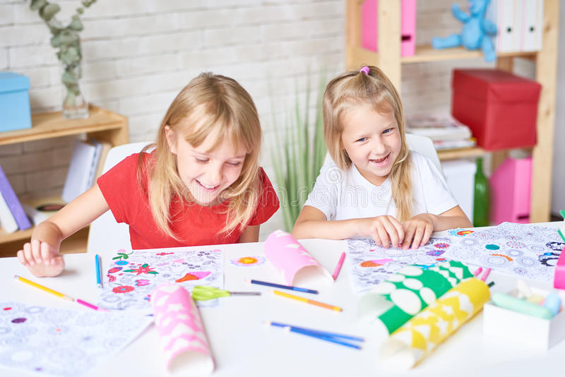 Lachende kleine Mädchen, die zusammen zeichnen lizenzfreies stockfoto