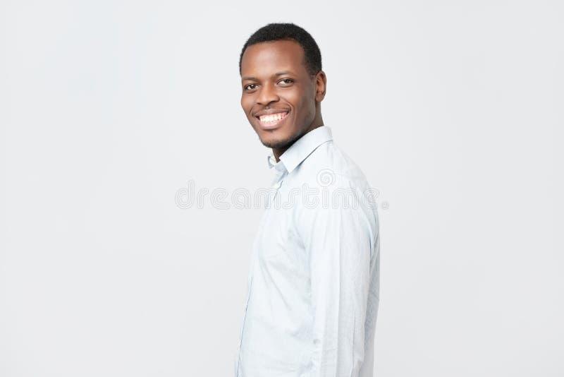 Lachende knappe jonge Afrikaanse mens in overhemd zeker glimlachen stock foto