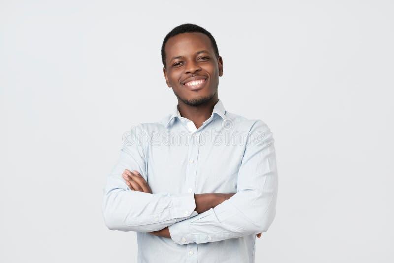Lachende knappe jonge Afrikaanse mens in overhemd zeker glimlachen stock fotografie