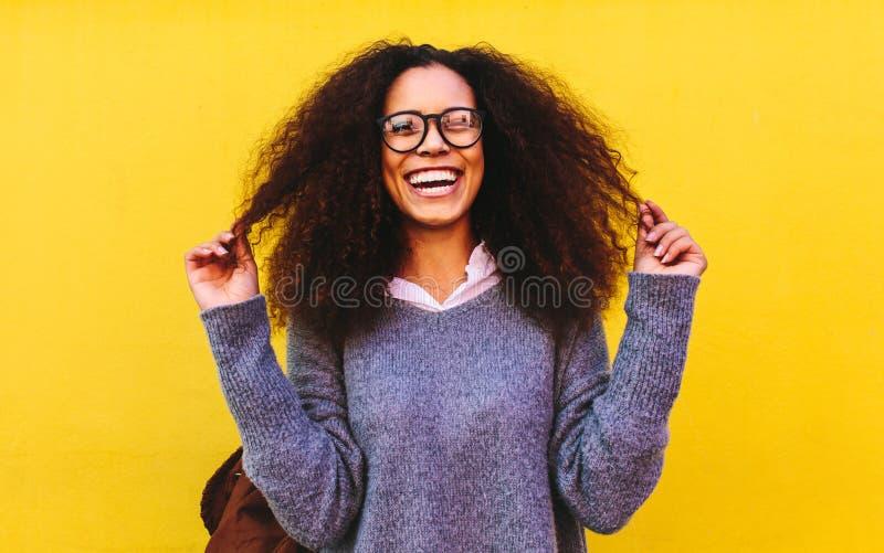 Lachende krullende haired vrouw op gele achtergrond stock afbeeldingen