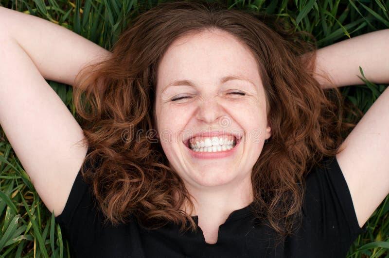 Lachende Lüge der Readhead Frau ein lizenzfreies stockbild
