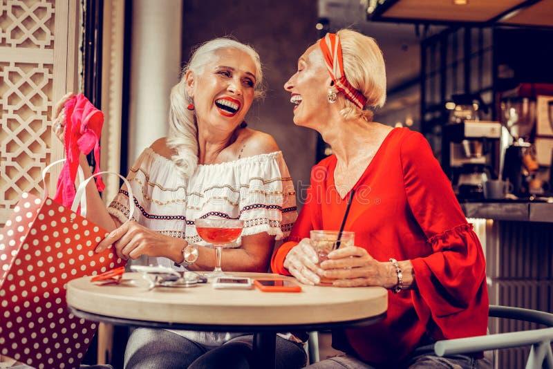 Lachende langharige vrouw die grappige gift van rode zak krijgen stock foto