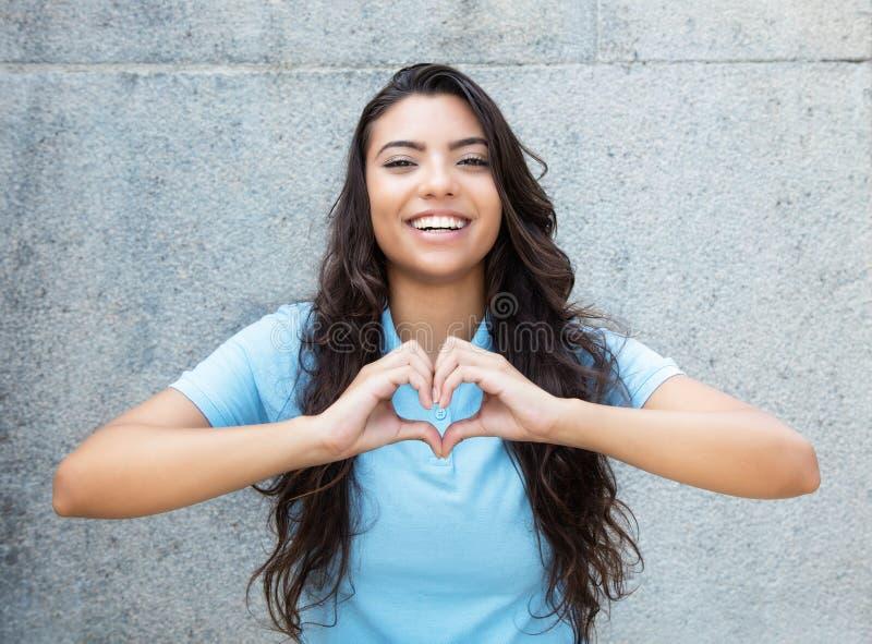 Lachende lateinamerikanische verliebte Frau, die Herz mit den Händen zeigt stockfoto