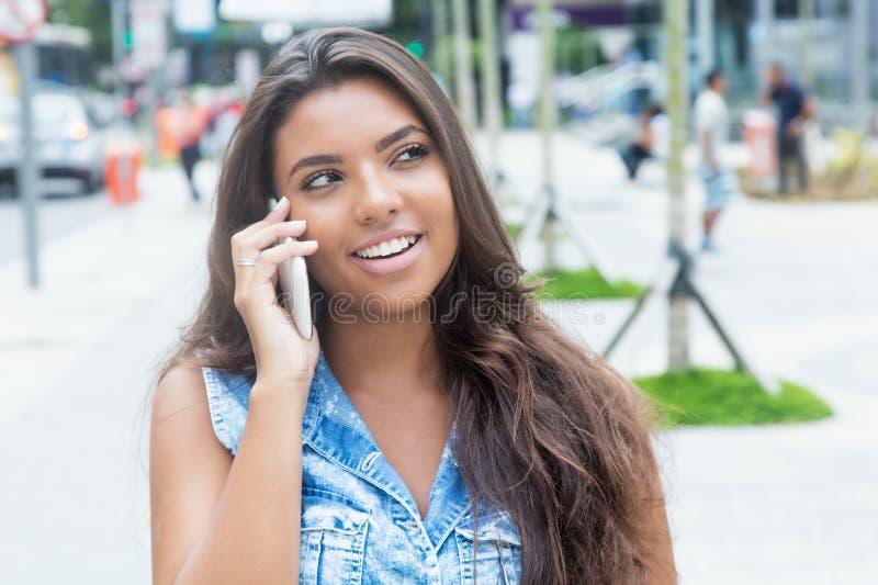 Lachende Latijnse vrouwelijke tiener bij slimme telefoon stock foto's