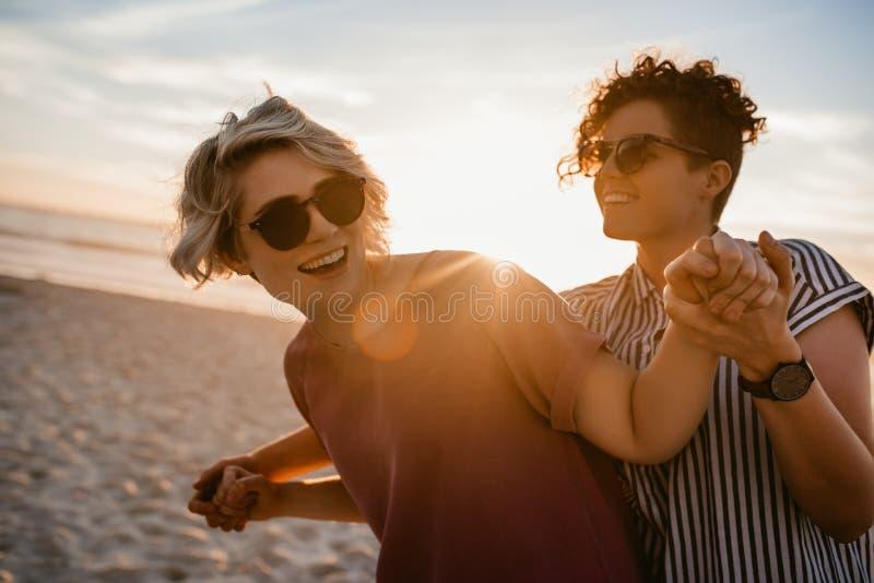 Lachende lesbische Paare, die zusammen auf einen Strand bei Sonnenuntergang tanzen stockfotografie