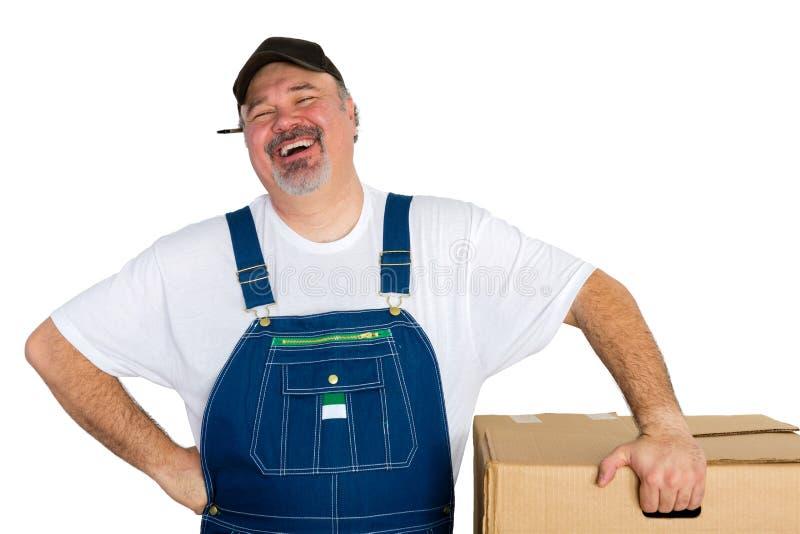 Lachende leveringsmens die zich door grote doos bevinden royalty-vrije stock foto's