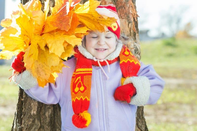 Lachende meisjeholding geel met oranje de bos in hand openluchtportret van de herfstbladeren stock afbeelding
