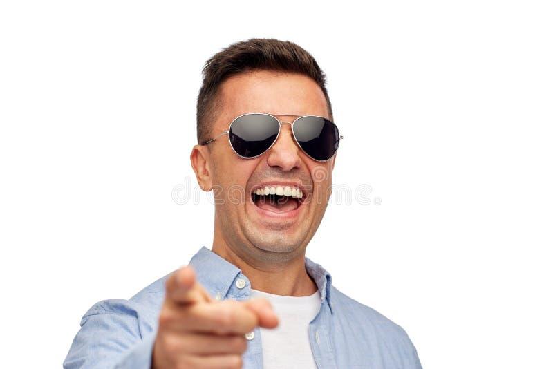 Lachende mens die in zonnebril vinger op u richten stock afbeeldingen