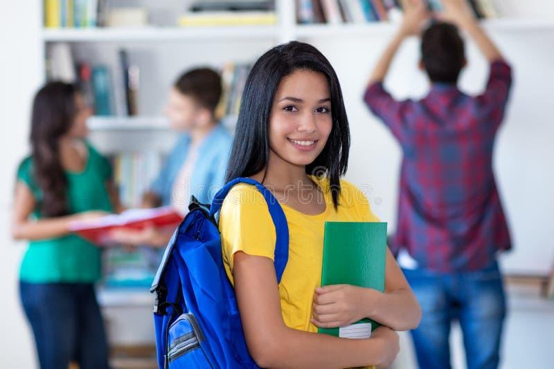 Lachende mexikanische Studentin mit Gruppe Studenten stockbild