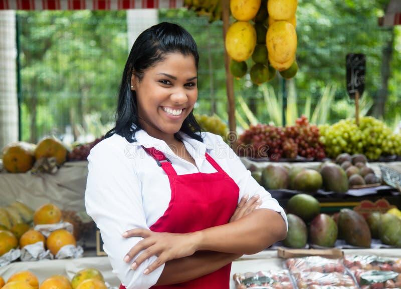 Lachende mexikanische Verkäuferin mit tropischen Früchten auf Landwirtmarkt stockbilder