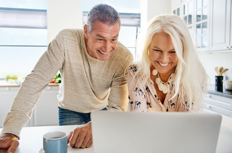 Lachende Mitte gealterte Paare, die Computer betrachten stockbilder