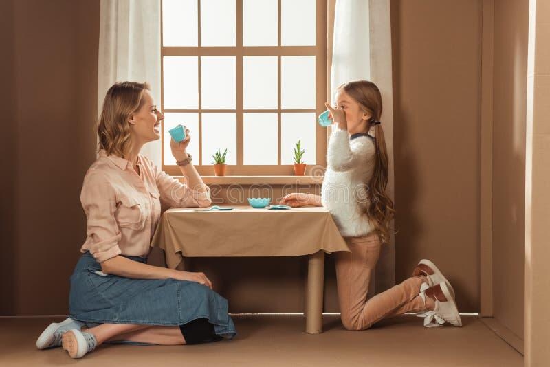 lachende moeder en dochter die theekransje hebben stock foto's