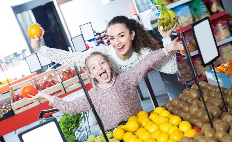 Lachende moeder en dochter het kopen vruchten royalty-vrije stock fotografie