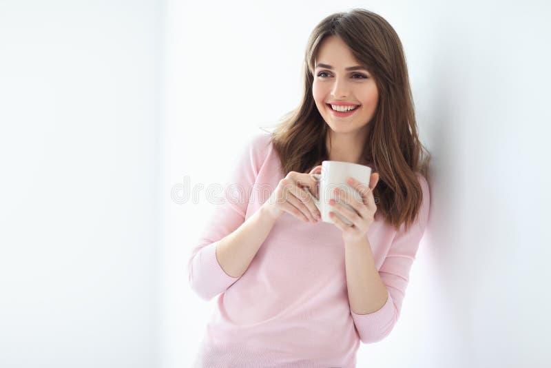 Lachende mooie vrouw met kop van koffie op witte achtergrond stock foto's