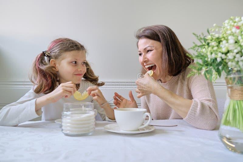 Lachende Mutter und Tochter, die von den Schalen und vom Essen der Zitrone trinken lizenzfreies stockfoto