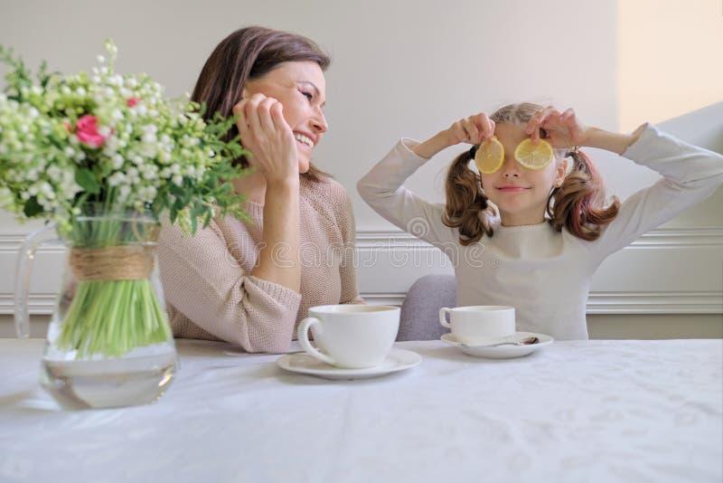 Lachende Mutter und Tochter, die von den Schalen und vom Essen der Zitrone trinken lizenzfreie stockfotografie
