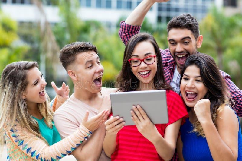 Lachende nerdy Franse vrouwelijke student met tabletcomputer en groep het toejuichen van internationale studenten royalty-vrije stock foto's
