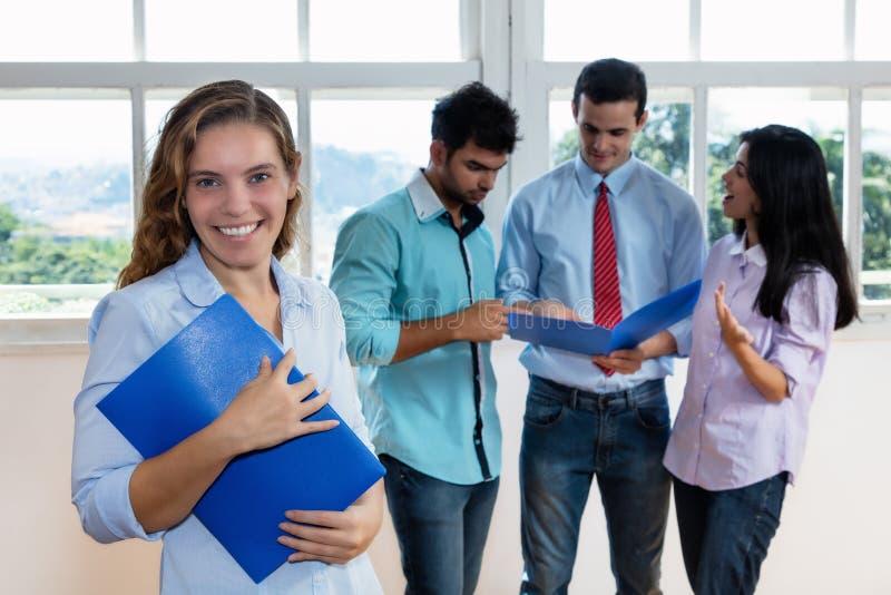 Lachende onderneemster met collega's stock afbeeldingen