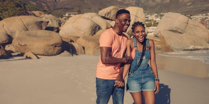 Lachende Paare auf Sommerferien am Strand stockbilder