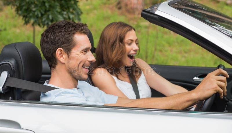 Lachende Paare, die in ein Silberkabriolett fahren lizenzfreie stockfotos