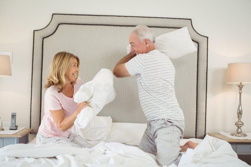 Lachende Paare, die Kissenschlacht auf Bett haben lizenzfreies stockfoto