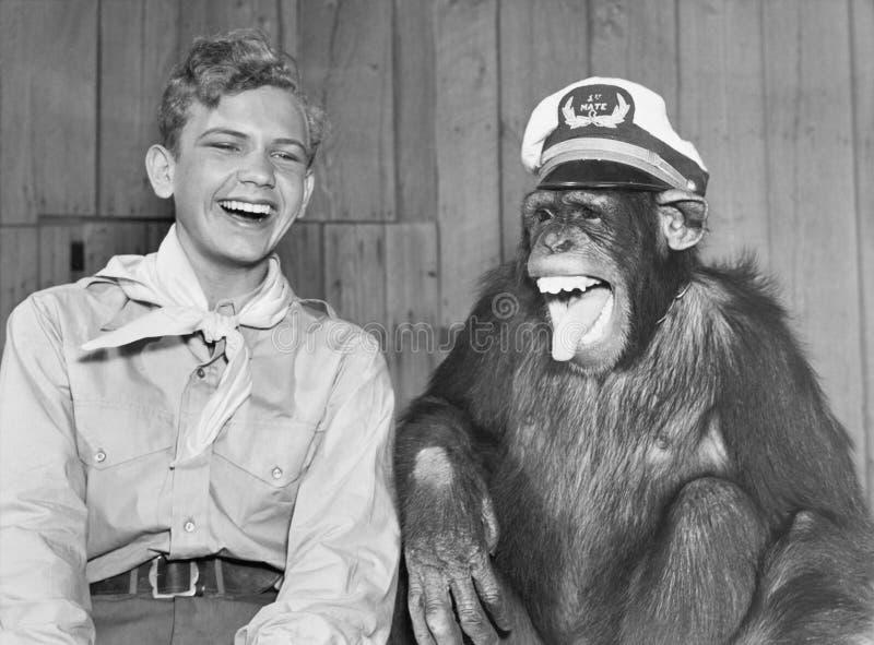 Lachende padvinder en aap die hoed dragen (Alle afgeschilderde personen leven niet langer en geen landgoed bestaat Leveranciersga stock afbeeldingen
