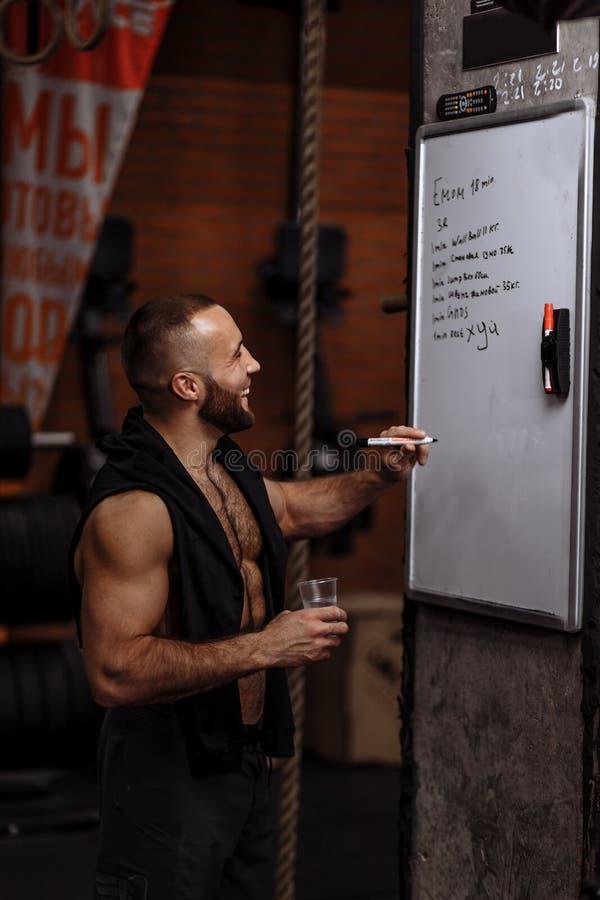 Lachende persoonlijke trainer die een glas water houden stock afbeelding