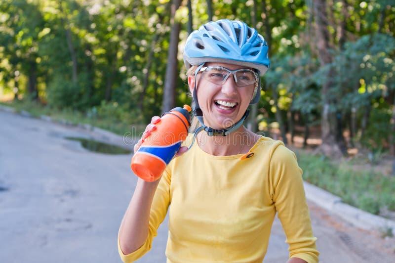 Lachende Radfahrerfrau draußen stockfotografie