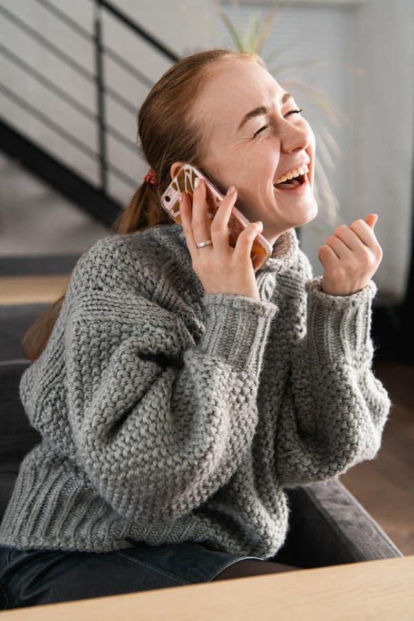 Lachende Rothaarige, die zu Hause auf der Couch hat ein Gespräch am Telefon sitzt lizenzfreie stockfotos