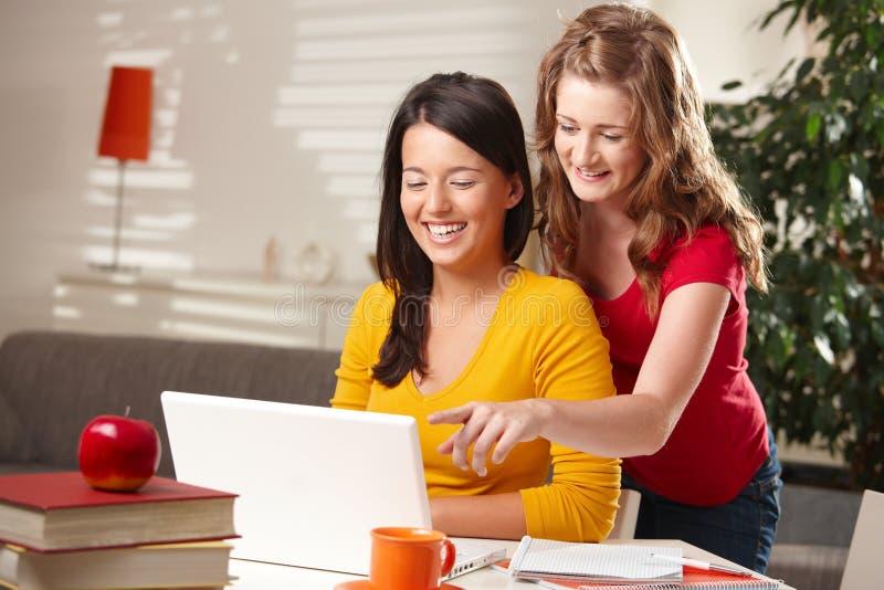 Lachende schoolmeisjes die computer bekijken royalty-vrije stock foto's