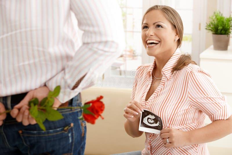 Lachende schwangere Frau, die Blumen erhält stockbild